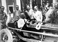 Mussolini sitting in an Alfa Romeo racing car prior to a competition. The Fascist regime allowed considerable autonomy to industries.