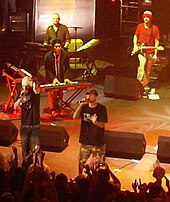 All-male group on stage, containing two MCs, two keyboardists, and a guitarist. Some of the crowd with hands in the air present in the foreground