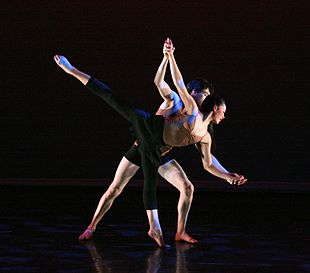 Dance Partnering A Male Dancer Assists A Female Dancer In Performing An Arabesque As Part Of A Classical Pas De Deux