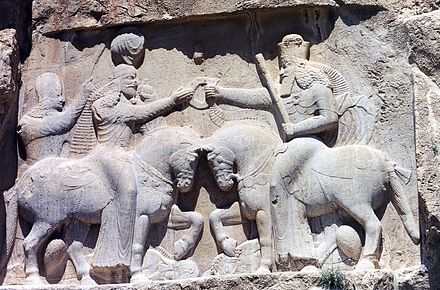 Ahura Mazda (depiction is on the right, with high crown) presents Ardashir I (left) with the ring of kingship. (Relief at Naqsh-e Rustam, 3rd century CE) Naqsh i Rustam. Investiture d'Ardashir 1.jpg