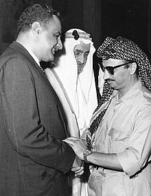 Two men facing and clasping each other's hands. On the right is a man in military uniform with sunglasses and a gun on his right side. On the left is a man wearing casual business suit. In the center, a man wearing a turban and a traditional Arab robe is facing the man on the right.