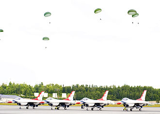 Arctic Thunder Air Show - As part of the Alaska Joint Forces demonstration, Army paratroopers land adjacent to the F-16 fighters of the Thunderbirds
