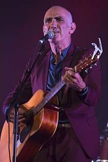 Head and shoulders of a sixty-year-old male standing at a microphone. He is strumming a guitar, singing and staring into the distance. He wears a purple suit, tie, blue shirt and vest.