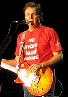 "McCartney, in his late sixties, playing an orange electric guitar and wearing a red shirt that bears, in white writing, the words ""no more land mines"". His eyes are closed."