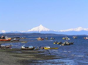 Fishing in Chile - Fishing boats in Quellón, Chiloé with Corcovado volcano in the background
