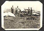 Photograph of a group of men around a crashed aircraft. (7980812263).jpg