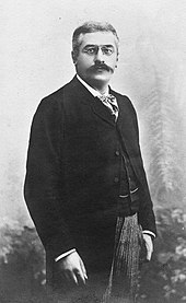 Driekwart lengte zwart-wit foto van een staande man, met grijzend haar, donkere wenkbrauwen en snor, bril, sjaal, wit overhemd, zwarte jas en geklede jas, lichte broek.