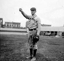 A black-and-white photograph of a man wearing an old-style baseball uniform and a newsie cap holding a baseball in his outstretched hand