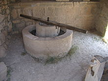 A reconstructed olive press from Volubilis consisting of a circular stone basin with a circular stone inset, atop which a long wooden bar is fixed