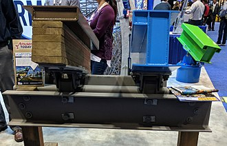 Rocky Mountain Construction - Topper Track (left) and I-Box Track (right) display at Rocky Mountain Construction's booth at IAAPA IAE 2017, with the T-Rex Track display behind them to the right