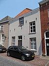 foto van Huis met witgepleisterde lijstgevel en hoog schilddak