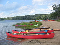 Photo of two red canoes on a sandy lake shore lined with trees. There are other canoes, kayaks and boats in the background, with a blue sky above.
