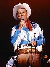 Roy Rogers dressed in cowboy gear sings into a microphone.