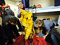 Royal Canadian Navy Able Seaman Ryan Nicholson, Petty Officer 2nd Class Michael Pinault-Lepage and Leading Seaman Emmie Penney remove and stow firefighting gear following emergency stations operations, similar 120504-N-IL267-008.jpg