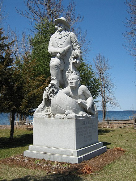 Champlain and guide[16] in Isle La Motte, Vermont, at the site Champlain is said to have first set foot in Vermont (and encamped) in 1609. Lake Champlain is in the background. (Sculptor E.L.Weber, 1967; Photo by Matt Wills, 2009)
