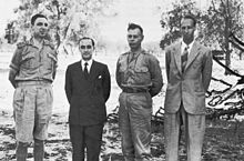 Four men pose awkwardly for a photograph. Two wear shirt-sleeve uniforms and the other two wear suits. All are bare-headed.