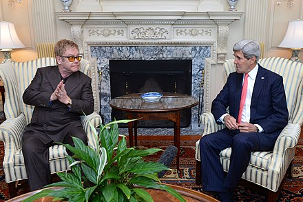 Elton John and United States Secretary of State John Kerry discuss AIDS relief and the work of the Elton John AIDS Foundation at the United States Department of State in Washington, D.C., 24 October 2014 Secretary Kerry and Sir Elton John (1).jpg
