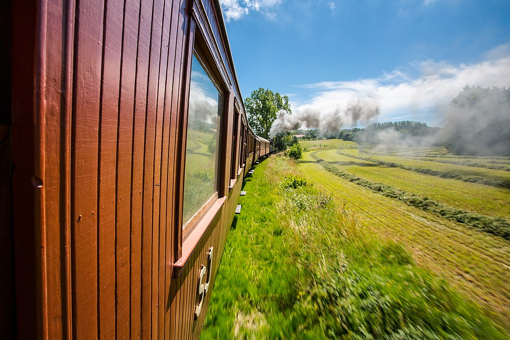 Rött tåg, grönt fält, blå himmel och rök från ångloket.