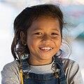 Smiling girl in sunshine wearing bib overalls in Laos at golden hour.jpg