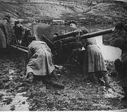 A large gun trapped in mud. Several men in long, heavy coats are pushing on it trying to get it free.