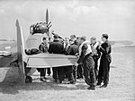 Squadron Leader P A Hunter (far left), the CO of No. 264 Squadron RAF, briefs his pilots by one of the Squadron's Boulton-Paul Defiants at Duxford, 31 May 1940. CH196.jpg