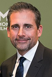 A man with black hair, Steve Carell, is standing in a tux. He is looking towards the camera and smiles.
