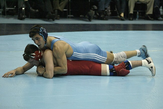 In collegiate wrestling, great emphasis is placed on one wrestler's control of the opponent on the mat, usually by controlling the opponent's legs or torso. When a wrestler gains control and maintains restraining power over an opponent, as seen here, he is said to be in the position of advantage. Students wrestling 10.jpg