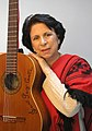 Suni Paz in a red poncho, holding her guitar.jpg