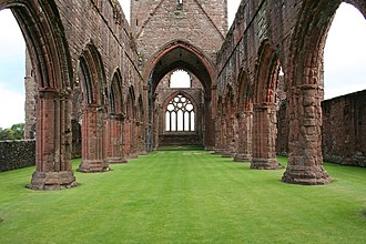 Sweetheart Abbey - Looking eastwards, the impressive nave of the abbey church leading (under the dramatic bell tower) to the chancel, with its richly carved and traceried windows. Above the rows of pillars, the triforia can just be seen.