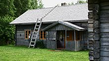 Rustic one-story wooden house with ladders to (and across) the roof