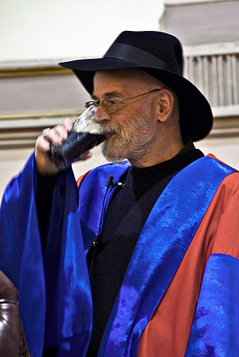 Pratchett drinking Guinness shortly after receiving an honorary degree from the University of Dublin in 2008 Terry Pratchett honorary degree TCD.jpg