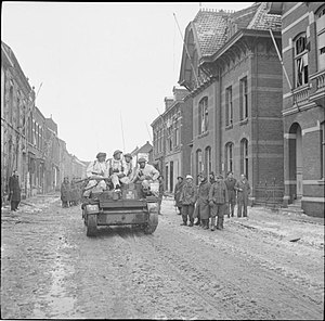 131st Infantry Brigade (United Kingdom) - Snow-suited troops of 131st Brigade, 7th Armoured Division, in Universal Carriers drive past German POWs in Echt, 18 January 1945.