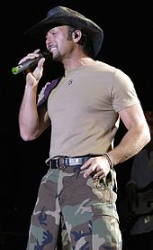 A man wearing a cowboy hat, light T-shirt and camouflage pants singing into a microphone