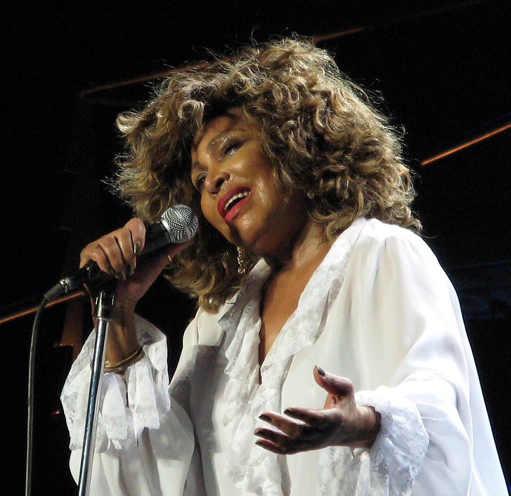 Tina Turner in red lipstick wearing a white top with floppy lace around the deep v neck line and blousy sleeves. Her hair is loose and she has one had on the stand microphone and the other outstretch, palm up.
