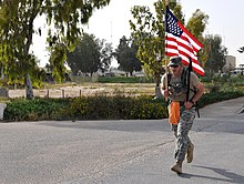 U.S. Army Sgt. Ross Paulsen, a medical maintenance specialist assigned to the Medical Company, 1st Support Battalion, Task Force Sinai, carries the American flag across the finish line during a Norwegian Road 140409-A-BE343-002.jpg