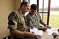 U.S. Army Staff Sgt. Jeremiah Green, right, and British army reserve Lt. Nicholaos Yiannakis grade tests taken by Burundi National Defense Force (BNDF) soldiers during a 10-day civil-military co-operation course 140320-F-CU844-141.jpg