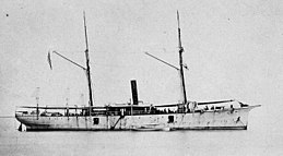 broadside view of a two-masted schooner with a smoke stack in the center, at anchor, without sails, painted white