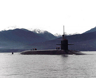 Submarine in bay with valleys and snow-capped mountains in the background.