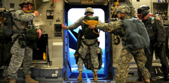 United States Army Jumpmaster School - An assistant jumpmaster stands in the door of a C-17 at an altitude of 1,200 feet, looking for terrain features identified as 1 minute or 30 second reference points.