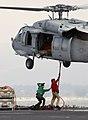 US Navy 031003-N-4768W-171 Photographer's Mate Airman Mark Rebilas, from Mesa, Ariz., photographs Chief Aviation Ordnanceman Darren Galbiso attaching a cargo pendant to the bottom of a MH-60S Knighthawk.jpg