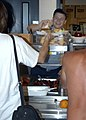 US Navy 050805-N-4008C-005 U.S. Navy Culinary Specialist Seaman Anthony Thompson, assigned to the amphibious assault ship USS Bataan (LHD 5), serves dinner to victims of Hurricane Katrina at Biloxi High School in Biloxi, Miss.jpg
