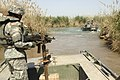 US Navy 060321-N-8252B-024 Master Sgt. Nardo Dedicatoria watches as a boat pulls out into the Euphrates River. Company E, 1st Battalion, 67th Armored Regiment performs a reconnaissance mission of the Musayyib Bridge.jpg