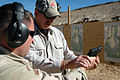 US Navy 061106-N-0888R-085 Retired Army veteran Art Campbell instructs Hospital Corpsman 1st Class Justin Davies the proper procedures when handling a 9mm during a weapons qualification course held during a joint task force exe.jpg