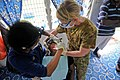 US Navy 090811-N-9689V-007 Marie Williams, a dentist from the University of California, and dental hygienist Australian Army, Cpl. Diane Beningfield, provide dental treatment to a patient.jpg