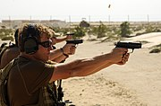 US Navy 100201-N-1291E-055 Explosive Ordnance Disposal Technician 2nd Class Robert Ganger, assigned to Explosive Ordnance Disposal Mobile Unit (EODMU) 11 fires his 9mm Pistol at a military shooting range in Bahrain