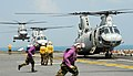 US Navy 110213-N-8607R-393 Aviation fuel crew members run to fuel a CH-46E Sea Knight helicopter aboard the forward-deployed amphibious assault shi.jpg