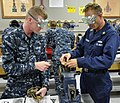 US Navy 110914-N-ZZ447-005 Machinist's Mate 1st Class Ryan Jacobsen, right, demonstrates proper maintenance procedures to Electrician's Mate Firema.jpg