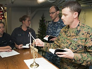 US Navy 111220-N-PB383-542 Hospitalman Aaron Seltzer, assigned to the 11th Marine Expeditionary Unit (11th MEU), lights a Menorah in observance of.jpg