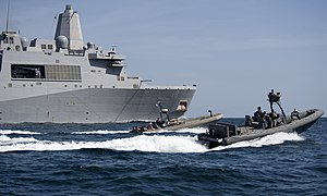 US Navy 120207-N-PB383-480 Sailors drive rigid hull inflatable boats past the amphibious transport dock ship USS New Orleans (LPD 18) during small.jpg