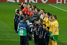 Celtic (foreground, in yellow) and Manchester United players (background, in red) and the match officials (in grey) line up prior to the group stage match between the two sides. Each player has a child mascot wearing a navy blue shirt standing in front of him, and a television camera crew is focusing on the Celtic players.